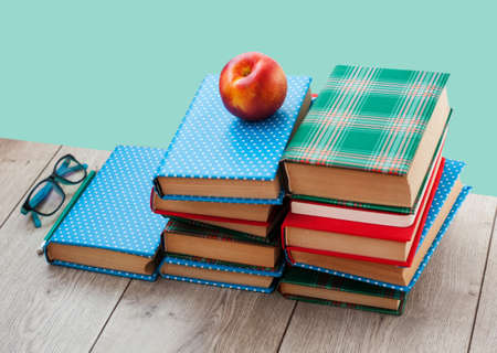 Back to school, pile of books in colorful covers and peach on wooden table with green mint background. Distance home education.Quarantine concept of stay home.