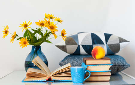 Cozy home interior decor: stack of books, peach, cup of coffe, decorative pillows and vase with yellow flowers on a table. Distance home education.Quarantine concept of stay home