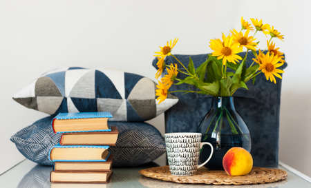 Cozy home interior decor: stack of books, peach, cup of coffe, decorative pillows, box with plaid and vase with yellow flowers on a table. Distance home education.Quarantine concept of stay home