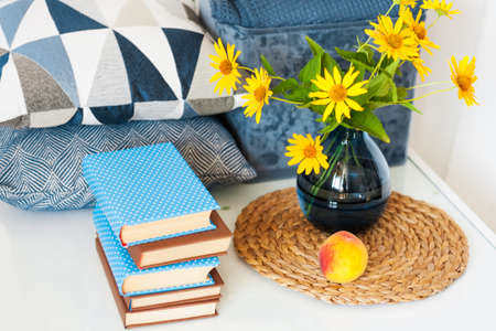 Cozy home interior decor: stack of books, peach, decorative pillows, box with plaid and vase with yellow flowers on a glass table. Distance home education.Quarantine concept of stay home