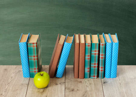 Back to school, pile of books in colorful covers and green apple on wooden table with empty green school board background. Distance home education.Quarantine concept of stay home