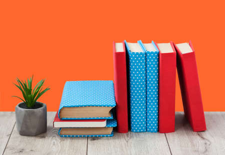 pile of books in colorful covers and plant in pot on wooden table on a orange background. Back to school distance home education.Quarantine concept of stay home