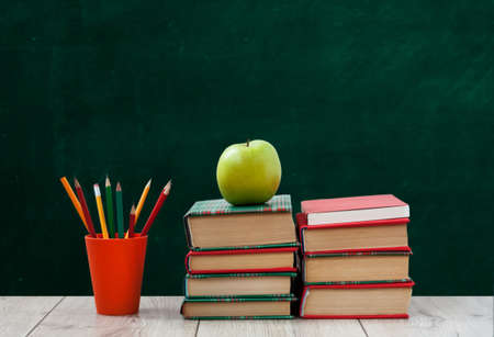 pile of books in colorful covers, pencils in holder and green apple on wooden table with green blackboard background. Distance home education. Back to school, quarantine concept of stay home Фото со стока
