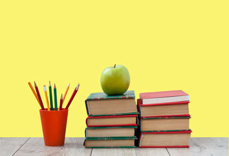 Books textbook in colorful covers on a yellow background. Back to school distance home education.Quarantine concept of stay home Фото со стока