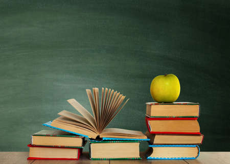 Open textbook, pile of books in colorful covers and green apple on wooden table with green blackboard background. Distance home education. Back to school, quarantine concept of stay home