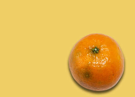 Fresh whole mandarin orange background (Citrus reticulata), clean tangerine on yellow background with copy space for text, healthy vegetarian diet top view
