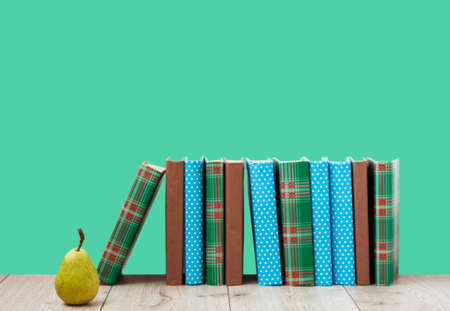 Open book textbook in colorful cover, pear on a green background. Back to school distance home education.Quarantine concept of stay home