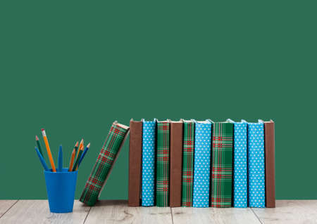 pile of books in colorful covers and pencils in holder on wooden table with green blackboard background. Distance home education. Back to school, quarantine concept of stay home