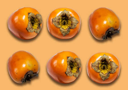 Fresh ripe whole persimmon, sharon on yellow orange background with copy space for text, healthy vegetarian diet top view Standard-Bild