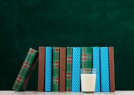 pile of books in colorful covers and glass of milk on wooden table with green blackboard background. Distance home education. Back to school, quarantine concept of stay home Standard-Bild