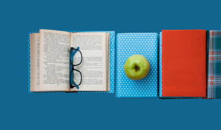 Open textbook, pile of books in colorful covers and apple on blue background. Back to school distance home education.