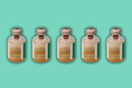 Medicine bottles with injection fluid with aluminum caps, coronavirus vaccine on green background. Covid epidemic, Cancer, painand diabetes treatment, pharmaceutical medicine concept