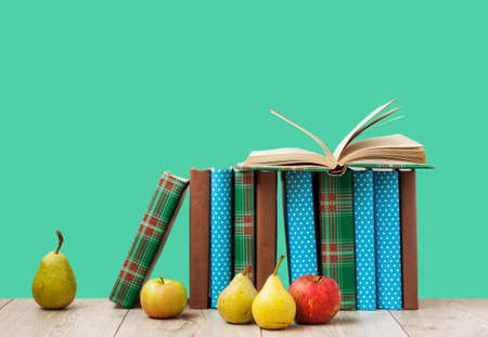 Open book textbook in colorful cover, pears and apples on a green background. Back to school distance home education.Quarantine concept of stay home Standard-Bild