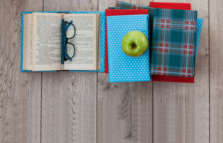 pile of books in colorful covers and apple on wooden table. Back to school distance home education.Quarantine concept of stay home.