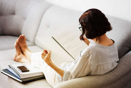 Middle-aged brunette woman with glasses on the gray sofa reading papers documents, business from home concept