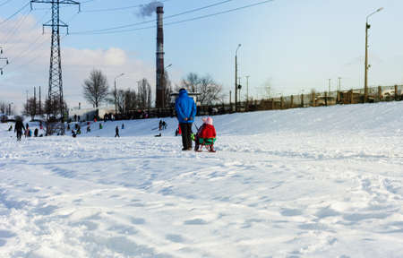 Children and their parents sledding from a snow slide in a city park with a frozen lake in Kiev, Ukraine