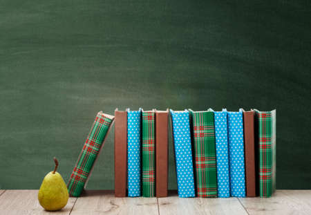 pile of books in colorful covers and pear on wooden table with green blackboard background. Distance home education. Back to school, quarantine concept of stay home