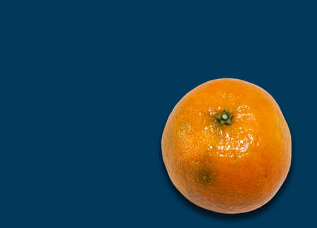Fresh whole mandarin orange (Citrus reticulata), clean tangerine on blue background with copy space for text, healthy vegetarian diet top view