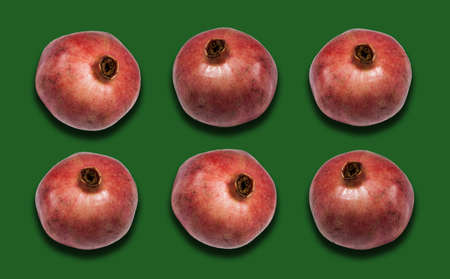 ripe red pomegranate fruit on green background with copy space for your text, healthy vegetarian diet top view