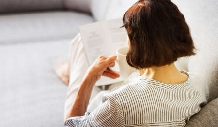 Middle-aged brunette woman with glasses on the gray sofa reading magazine with cup of coffee, soft focus