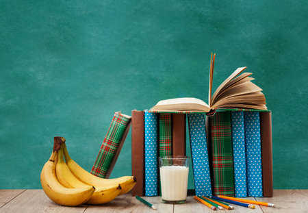 Open textbook, pile of books in colorful covers, pencils, bananas and a glass of milk on wooden table with green blackboard background. Distance home education. Back to school, concept of stay home