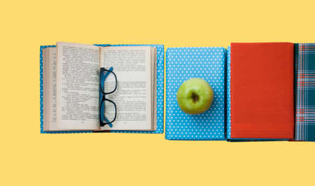 Open textbook, pile of books in colorful covers and apple on yellow background. Back to school distance home education.