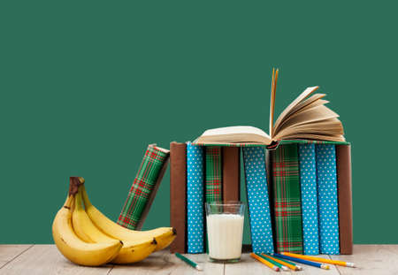 Open book textbook in colorful cover, banana and a glass of milk on a green background. Back to school distance home education.Quarantine concept of stay home Standard-Bild