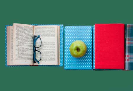 Open textbook, pile of books in colorful covers and apple on green background. Back to school distance home education.