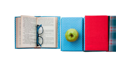 Open textbook, pile of books in colorful covers and apple on white background. Back to school distance home education. Standard-Bild