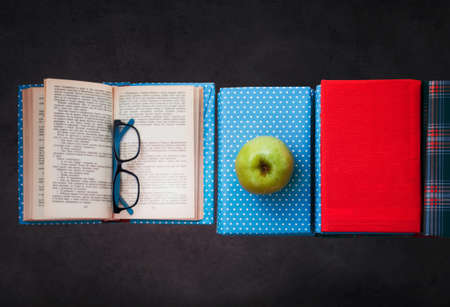 Open textbook, pile of books in colorful covers and apple with blackboard background. Distance home education. Back to school, quarantine concept of stay home