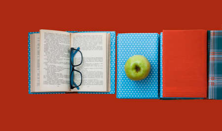 Open textbook, pile of books in colorful covers and apple on red pink orange background. Back to school distance home education.