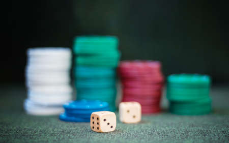 Casino poker chips stack dice on green felt background