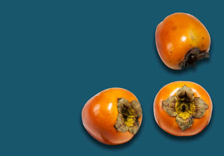 Fresh ripe whole persimmon, sharon on blue background with copy space for text, healthy vegetarian diet top view