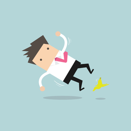 Businessman slipping on a banana peel and falling down