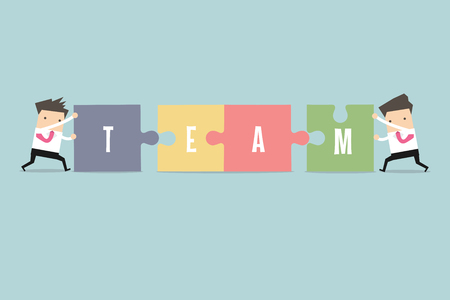 cooperating: Businessman pushing jigsaw pieces with the word team