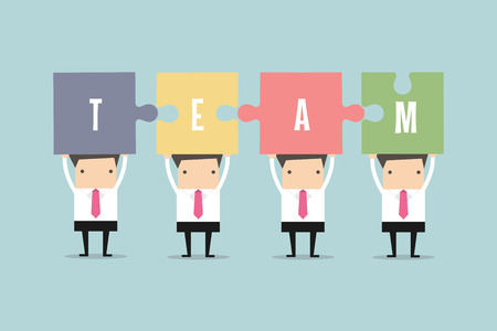 businessmen with jigsaw pieces with the word team