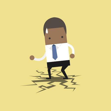 African businessman standing on cracking floor.