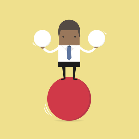 African businessman balancing on red ball holding two spheres.