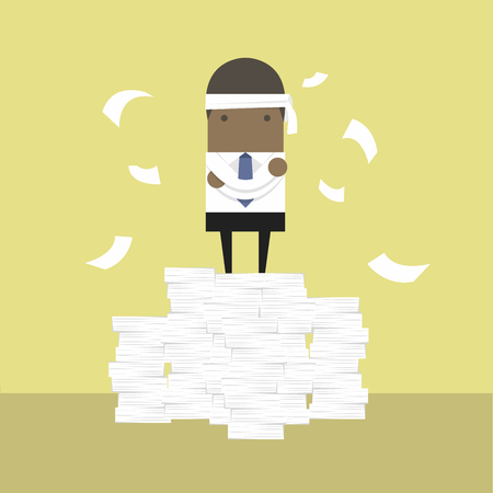African businessman standing on paperwork.