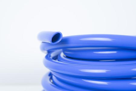 Blue plastic hose close up on white background.
