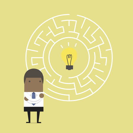African businessman in front of a huge maze and finding direction to idea bulb.