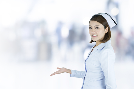 Asian smiling nurse presenting, showing her hand to blank space in hospital blurred background.