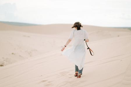 Young female exploring the desert, sandy beach camera.