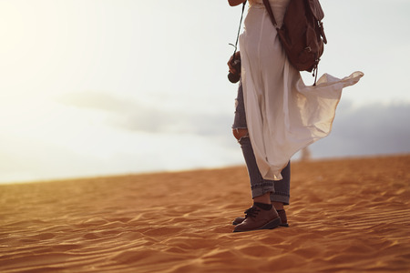 Young female exploring the desert, sandy beach with bag and camera.