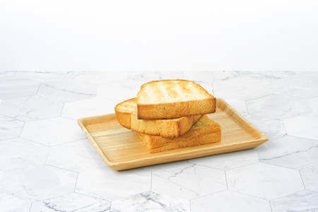 Slices toast bread in wooden dish on table.