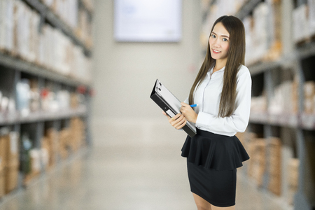 Asian business woman checking list order on a warehouse.