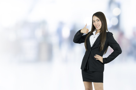 Smiling asian young business woman with thumb up on blurred background.