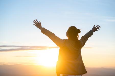 Glückliche Frau, die allein mit erhobenen Armen während des schönen Sonnenaufgangs am Morgen steht.