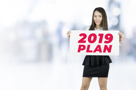 Businesswoman holding placards with 2019 Plan sign.