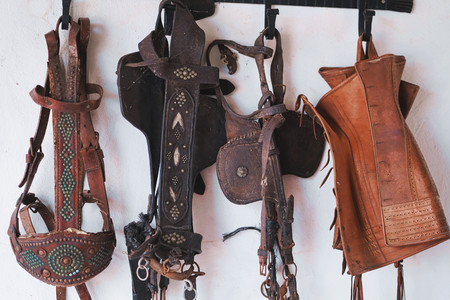Leather horse bridles and bits hanging on wall. Imagens - 122182796